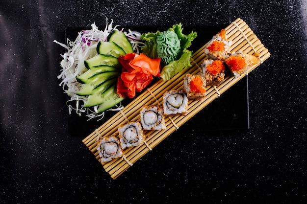 Rollos de sushi en una estera de sushi con wasabi, jengibre y pepino.