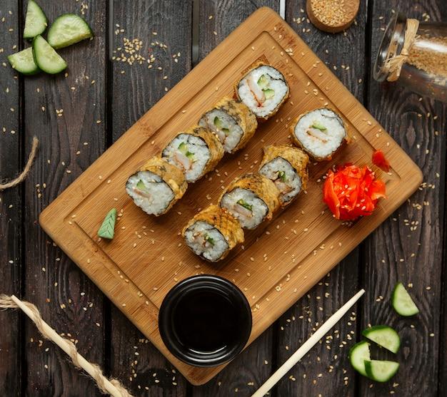 Rollos de sushi fritos con camarones y pepino servidos con wasabi y jengibre