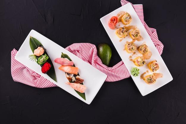 Rollos de sushi y gunkan en un plato blanco rectangular sobre una superficie negra (vista superior)