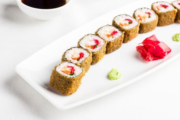 Rollos de sushi japonés con carne de cangrejo sobre fondo blanco