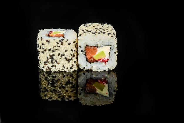 Rollos de sushi japonés fresco tradicional sobre un fondo negro