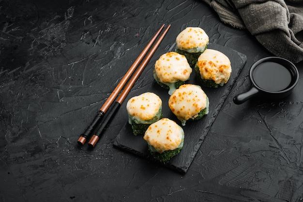 Rollos de sushi japonés llamado baked ebi con wasabi y pescado de salmón, sobre mesa de piedra negra