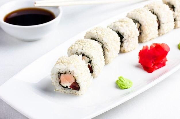 Rollos de sushi japonés con salmón en rica y sésamo sobre fondo blanco