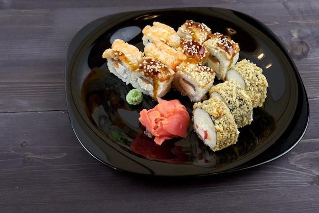 Rollos de sushi con jengibre y wasabi en un plato negro