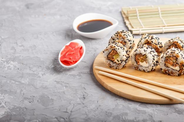 Rollos de sushi maki japonés con salmón y sésamo pepino sobre tabla de madera sobre un fondo de hormigón gris