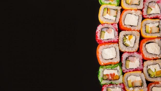 Rollos de sushi con pepino y aguacate con fondo de frontera de alimentos de verduras crudas