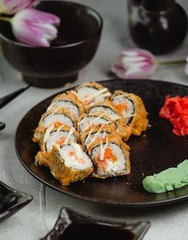 Rollos de sushi en placa blac con tulipanes alrededor.