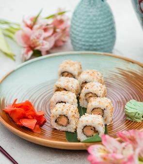 Rollos de sushi en placa verde marrón con jengibre y wasabi.