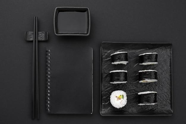 Rollos de sushi en plato con cuaderno y palillos
