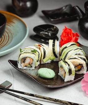 Rollos de sushi en un plato negro con palillos.