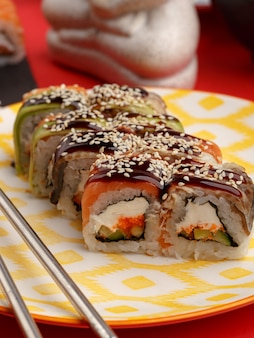 Rollos de sushi en platos de colores sobre un fondo rojo.