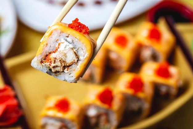 Rollos de sushi con queso crema de pollo arroz caviar rojo seta vista lateral