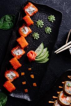 Rollos de sushi rojo con wasabi, jengibre y pepino en plato negro.