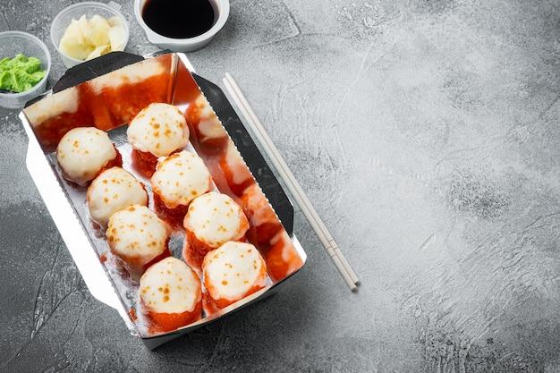 Rollos de sushi sabroso en cajas desechables, sobre mesa de piedra gris