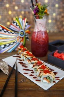 Rollos de sushi con salmón y pepino cubiertos con aguacate