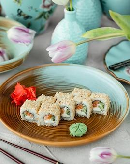 Rollos de sushi con salmón, queso crema, cucuber cubierto con sésamo