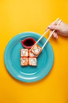 Rollos de sushi con salmón sobre un fondo negro con salsa de soja y una mano de mujer con palillos sobre un fondo amarillo