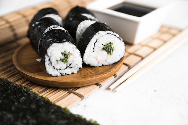 Rollos de sushi y salsa de soja sobre estera de bambú