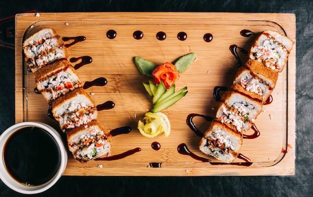 Rollos de sushi con salsa de soja sobre una plancha de madera.