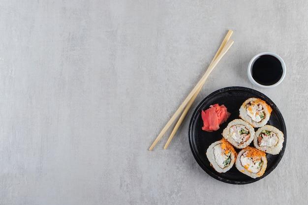 Rollos de sushi, salsa de soja, wasabi y jengibre encurtido sobre mesa de piedra.
