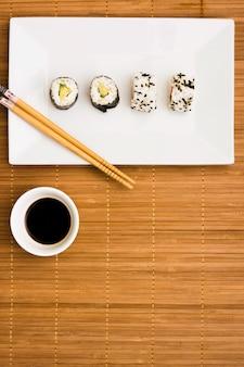 Rollos de sushi saludables en un plato con palillos y salsa de soja oscura sobre mantel
