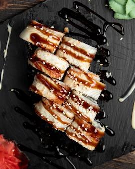 Rollos de sushi con semillas de sésamo y salsa