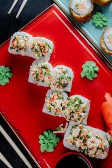 Rollos de sushi servidos con wasabi y jengibre