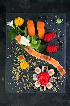 Rollos y sushi sobre un fondo de pizarra negra, cocina japonesa.