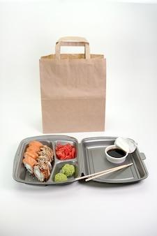 Rollos de sushi surtidos en una pared blanca aislada. entrega de cocina japonesa