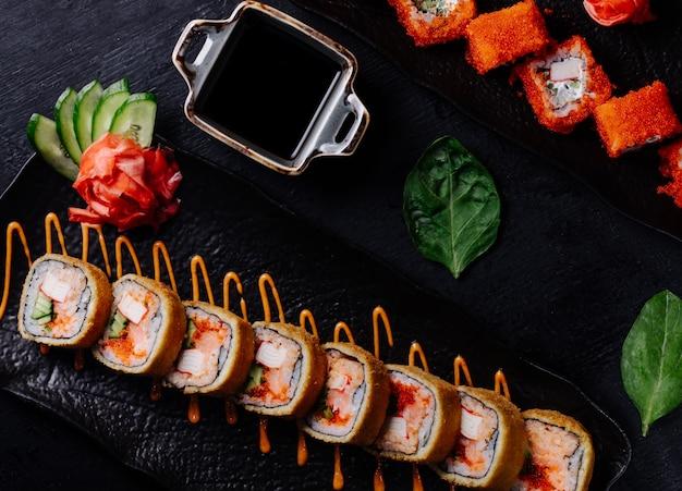 Rollos de sushi variedades en plato negro con salsa de soja.
