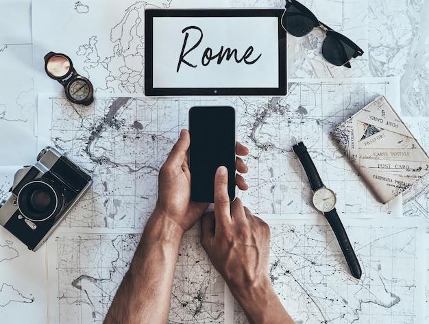 Roma. cerrar vista superior del hombre con teléfono inteligente con gafas de sol, cámara fotográfica, brújula