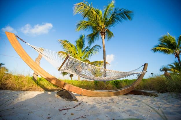 Romántica hamaca a la sombra de palmeras en playa tropical