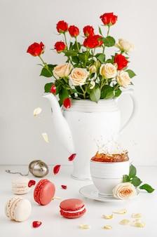 Romántica mesa de desayuno con ramo de rosas, pétalos voladores, salpicaduras de té y macarons