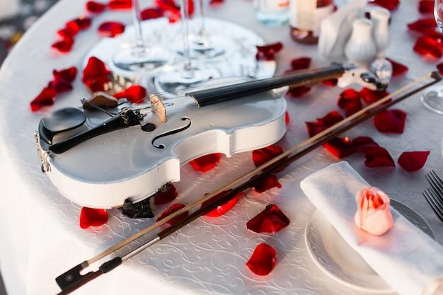 Romántica mesa de san valentín con vino, platos, vasos vacíos, pétalos de rosa, velas, violín