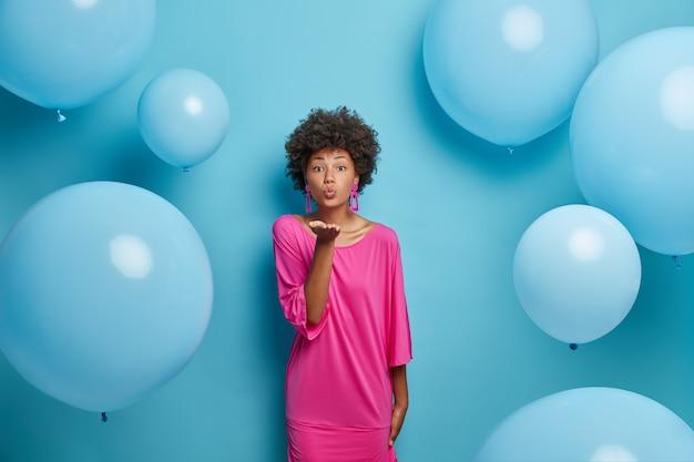Romántica mujer afroamericana envía beso al aire, expresa amor y afecto, usa elegante vestido rosa, posa