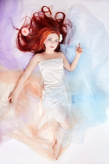 Romántica mujer con cabello largo y vestido de nube. mujer soñando maquillaje brillante y cuerpo perfecto. mujer pelirroja en vestido de color claro y aireado se encuentra en el suelo. hermosas flores en cabello de mujer