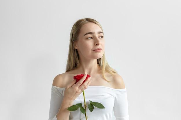Romántica mujer caucásica joven con hombros abiertos vestido de manga larga sosteniendo una rosa roja del chico en la primera cita, mirando hacia los lados con una misteriosa sonrisa de ensueño. amor, pasión y romance