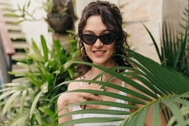 Romántica mujer feliz con cabello corto y rubio ojos cerrados y disfrutando de las vacaciones en un día caluroso de verano en la isla en la pared de plantas exóticas