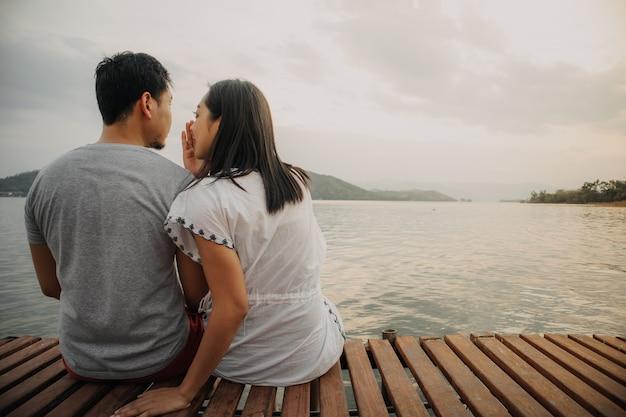 Romántica pareja asiática que susurra y disfruta de la vista al lago.