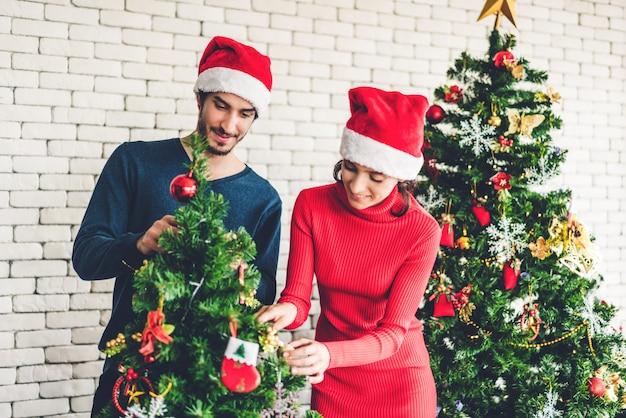 Romántica pareja dulce con sombreros de santa divirtiéndose decorando el árbol de navidad y sonriendo mientras celebra la víspera de año nuevo y disfruta de pasar tiempo juntos en navidad en casa
