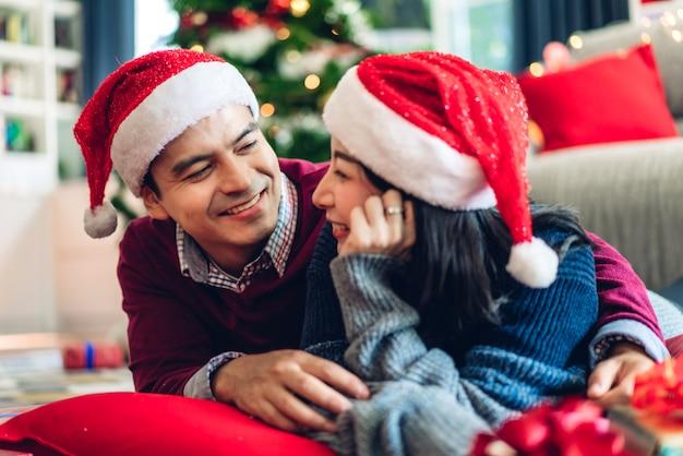 Romántica pareja dulce con sombreros de santa divirtiéndose y sonriendo mientras celebra la víspera de año nuevo y disfruta pasar tiempo juntos