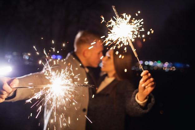 Romántica pareja de enamorados celebra la vida nocturna de fiesta con bengala de fuego
