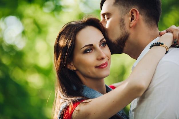Romántica pareja de enamorados, sonriendo y abrazándose en el jardín