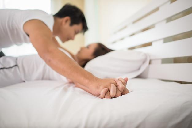 Romántica pareja feliz en la cama disfrutando de los juegos previos sensuales.