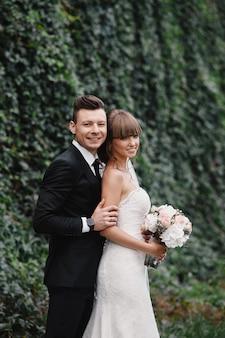 Romántica pareja feliz recién casados, novia y el novio se encuentra y con ramo de flores de color rosa y morado y verdes, vegetación con cinta en el jardín. ceremonia de boda en la naturaleza.