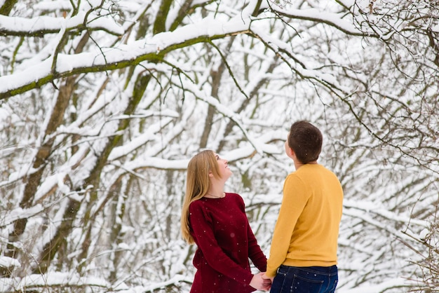 Romántica pareja joven cogidos de la mano al aire libre