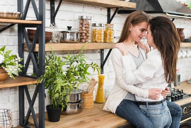 Romántica pareja de lesbianas jóvenes en la cocina.