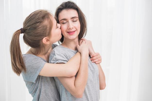 Romántica pareja de lesbianas jóvenes de pie contra la cortina blanca