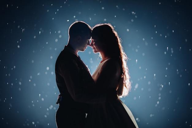 Romántica pareja de recién casados abrazándose cara a cara contra un fondo oscuro iluminado con destellos brillantes alrededor.