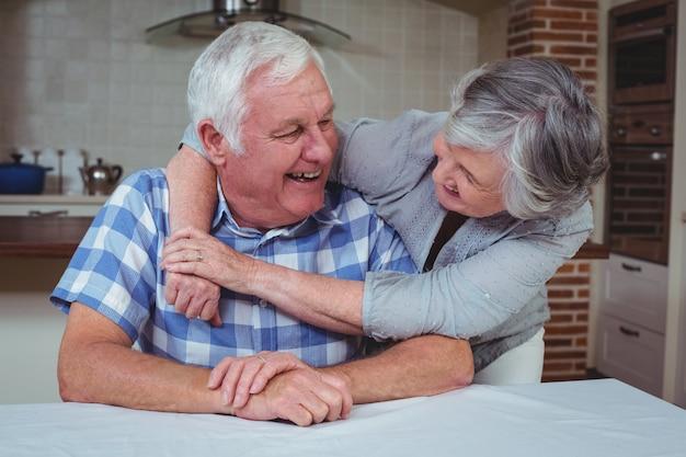 Romántica pareja senior abrazando en cocina